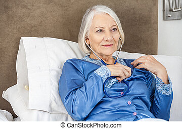 Senior Woman Listening To Her Heartbeat Through Stethoscope