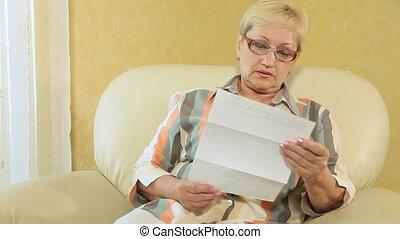 Senior woman looking at a bank statement