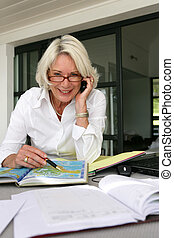 Senior woman looking at a map whilst on the phone