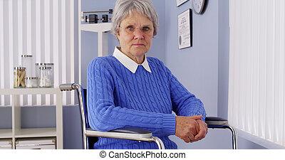 Senior woman looking at camera in wheelchair