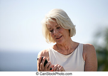 Senior woman looking at her cellphone