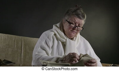 looking at old photographs - Senior woman looking at old...