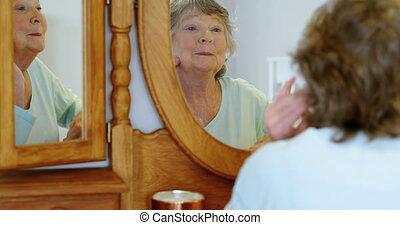 Senior woman looking face in mirror 4k - Senior woman...