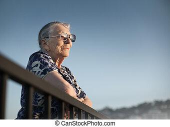 Senior woman looking forward over blue sky.