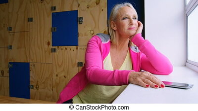 Senior woman looking out through window in fitness studio 4k...