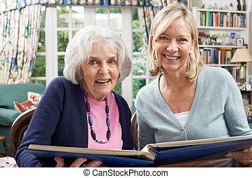 Senior Woman Looks At Photo Album With Mature Female...
