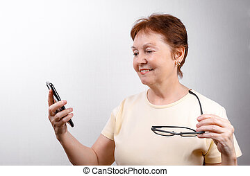 senior woman looks at the phone with glasses on a white background in a light T-shirt. place for text, isolated