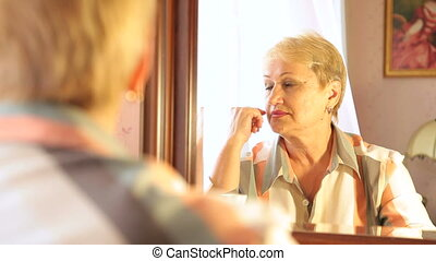 Pensive senior woman looking into mirror at herself