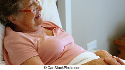 Senior woman lying on bed at home 4k