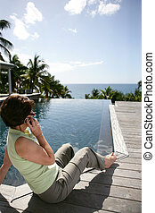 Senior woman making a call by the pool