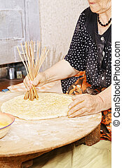Senior woman making holes in bread