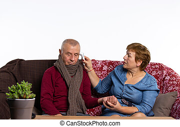 Senior woman measures fever with a thermometer to sick husband. Fighting a viral infection at home.