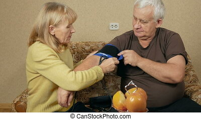 Senior woman measures the blood pressure of a man at home on the couch.
