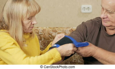 Senior woman measures the blood pressure of a man at home on the couch. She wears a cuff on your arm and listen to the pulse sphygmomanometer. The concept of health