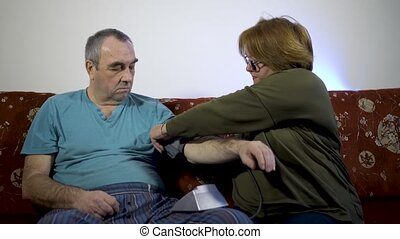 Senior woman measures the blood pressure of a man at home on the couch. The concept of health