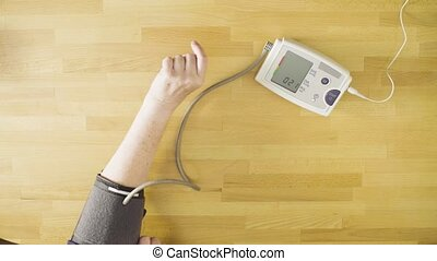 Senior woman measuring her own blood pressure - Top view....