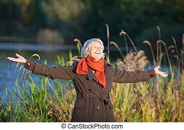 senior woman, med, beväpnar outstretched, avnjut, solljus