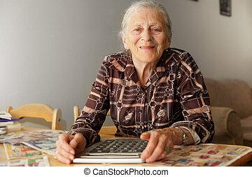senior woman, med, stor, räknemaskin