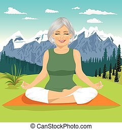 senior woman meditating and exercising yoga lotus position in mountains