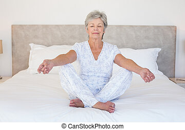 Senior woman meditating in bed