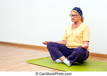 Senior woman meditating in gym.