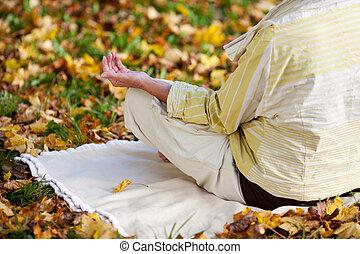 Senior Woman Meditating In Lotus Position At Park
