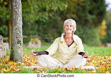 Senior Woman Meditating In Lotus Position