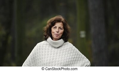 Senior woman on a walk in autumn forest, posing