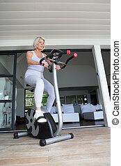 Senior woman on an exercise bike