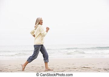 Senior Woman On Holiday Running Along Winter Beach