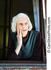 Senior woman on the house window
