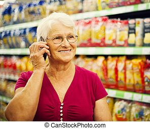 Senior woman on the phone at supermarket