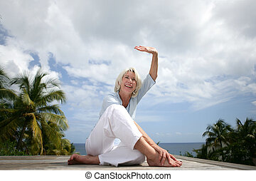 senior woman on vacation doing exercises