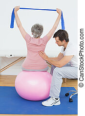 Senior woman on yoga ball with a physical therapist - Senior...