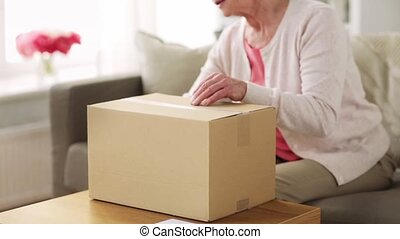 senior woman opening parcel box at home - delivery, mail,...