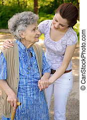 Senior woman outdoors - Senior woman walking with the help ...