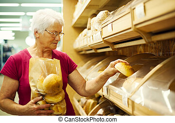 Senior woman packing buns at supermarket
