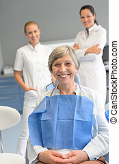 Senior woman patient with professional dentist team