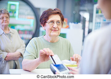 Senior woman paying with credit card in pharmacy