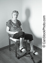 Senior woman pedaling sitting on a chair