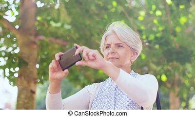 senior woman photographing at summer park