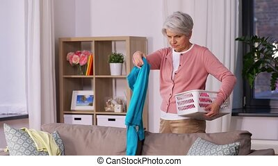 senior woman picking clothes for laundry at home - housework...
