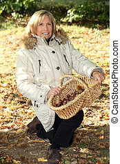 Senior woman picking mushrooms