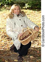 Senior woman picking mushrooms