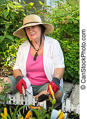 Senior woman planting flowers in the garden