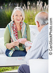 Senior Woman Playing Cards With Man