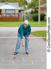 Senior woman playing hopscotch