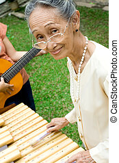 active asian elderly woman playing kolintang (wooden xylophone of the Northern Celebes), a traditional musical instrument from Indonesia.