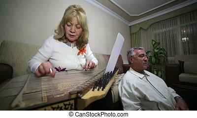 Senior woman playing qanun instrument
