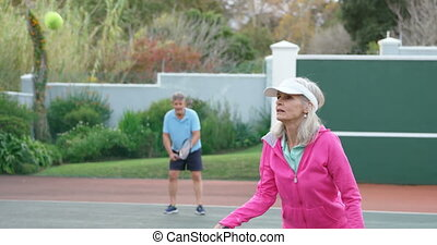 Senior woman playing tennis in tennis court 4k - Concentrate...